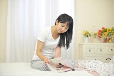 ベッドで雑誌を読んでいる女性